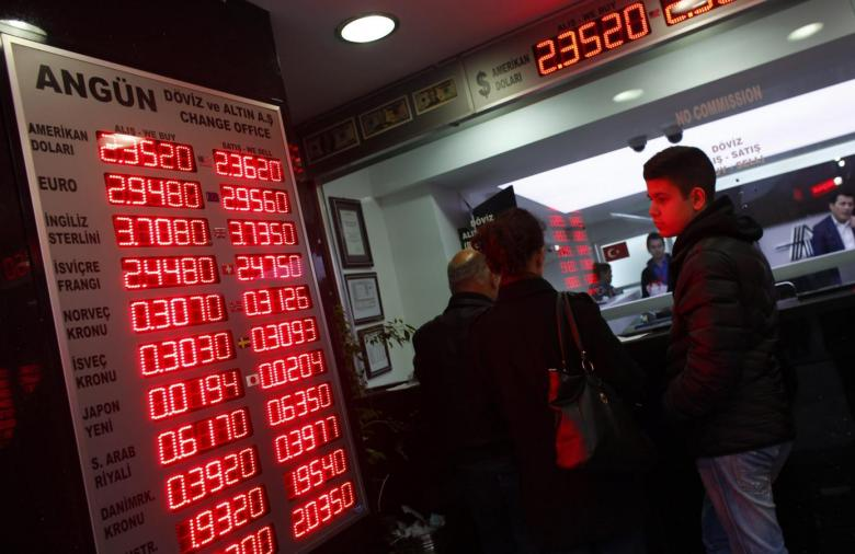 People check currency exchange rates at an currency exchange office in Istanbul December 16, 2014. REUTERS/Murad Sezer